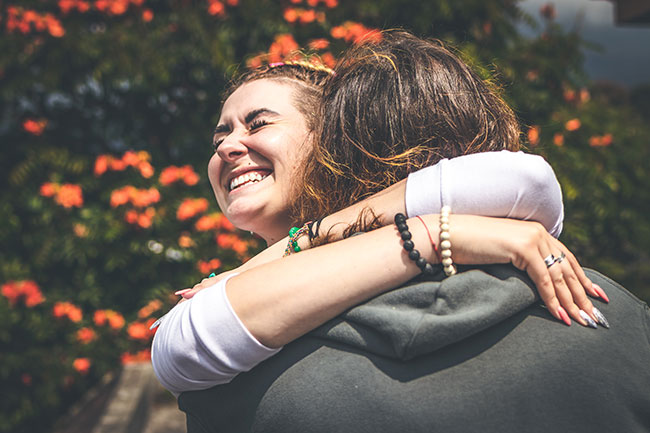 smiling-woman-hugging-another-person